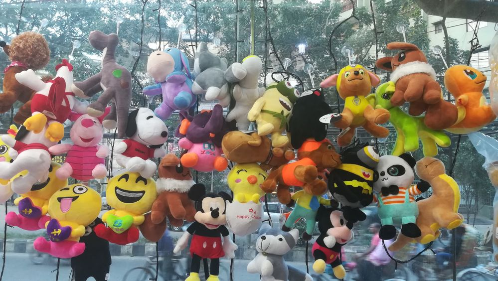 Dolls hanging on the glass wall...