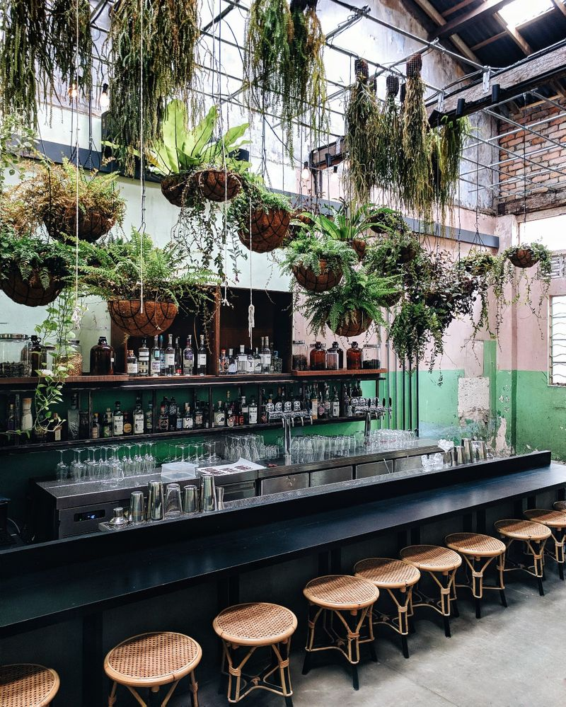 Caption: The interior of Botakliquor, an airy bar with hanging plants in in Kuala Lumpur, Malaysia.