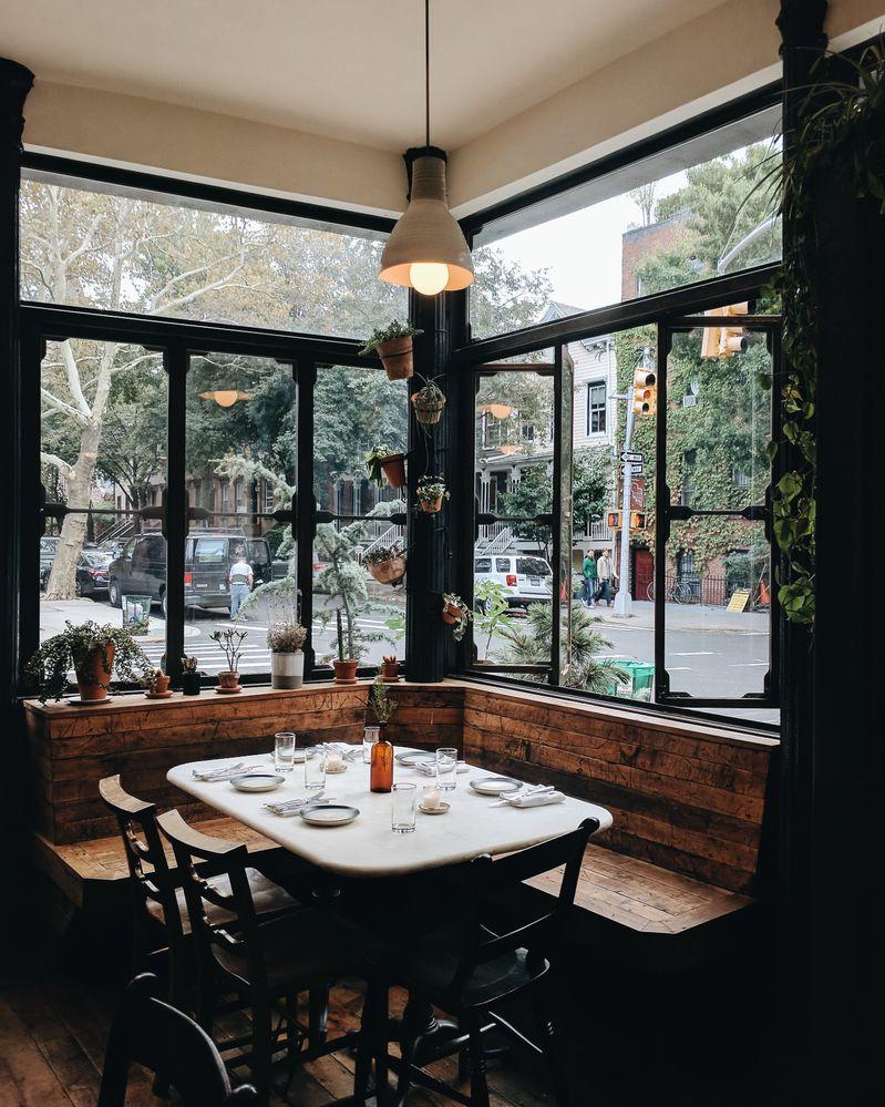 Caption: Light streams through the windows at Mettā, a restaurant in Brooklyn.